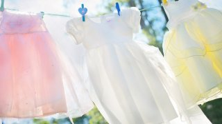 pink, white, and yellow dresses hanging on a clothesline