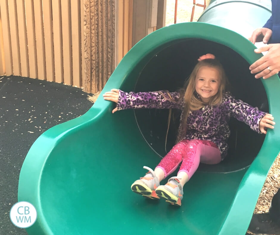 6 year old girl going down a tube slide