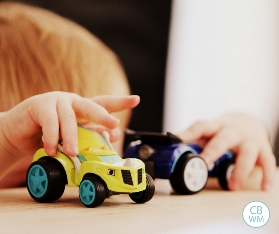 Child playing with toy cars at the table