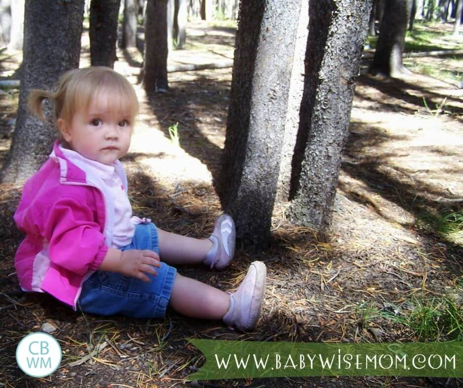 Toddler girl sitting in the forest in Yellowstone