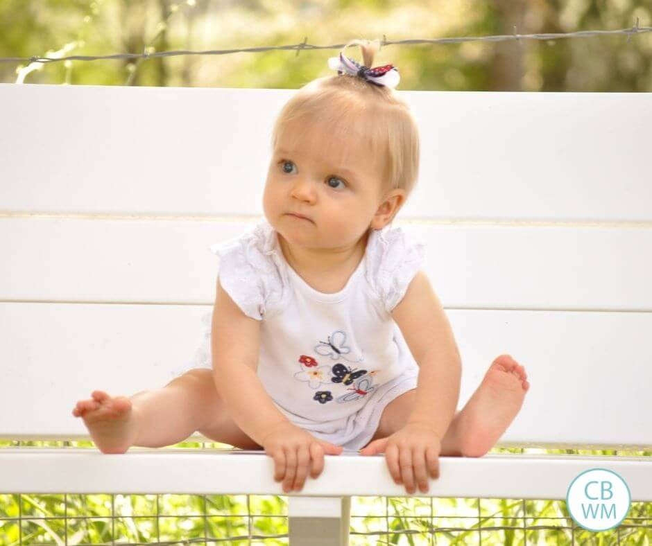 Brinley sitting on a bench at 11 months old