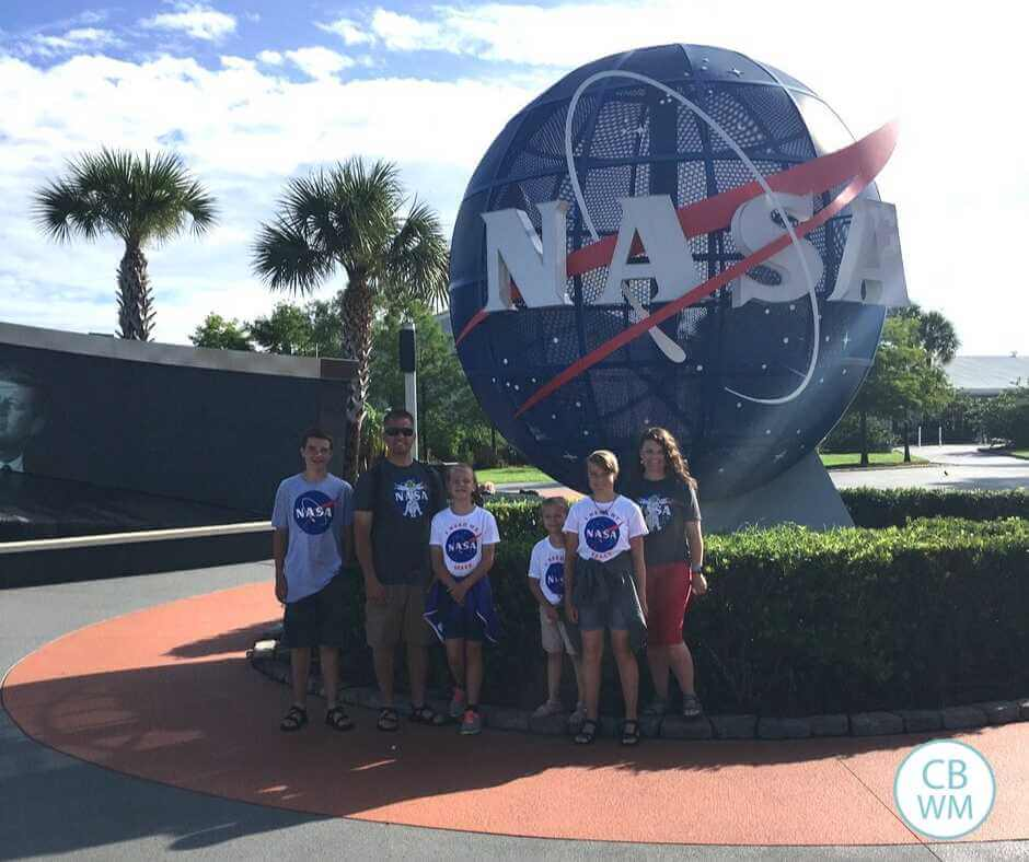 A family standing outside Kennedy Space Center in front of the NASA globe