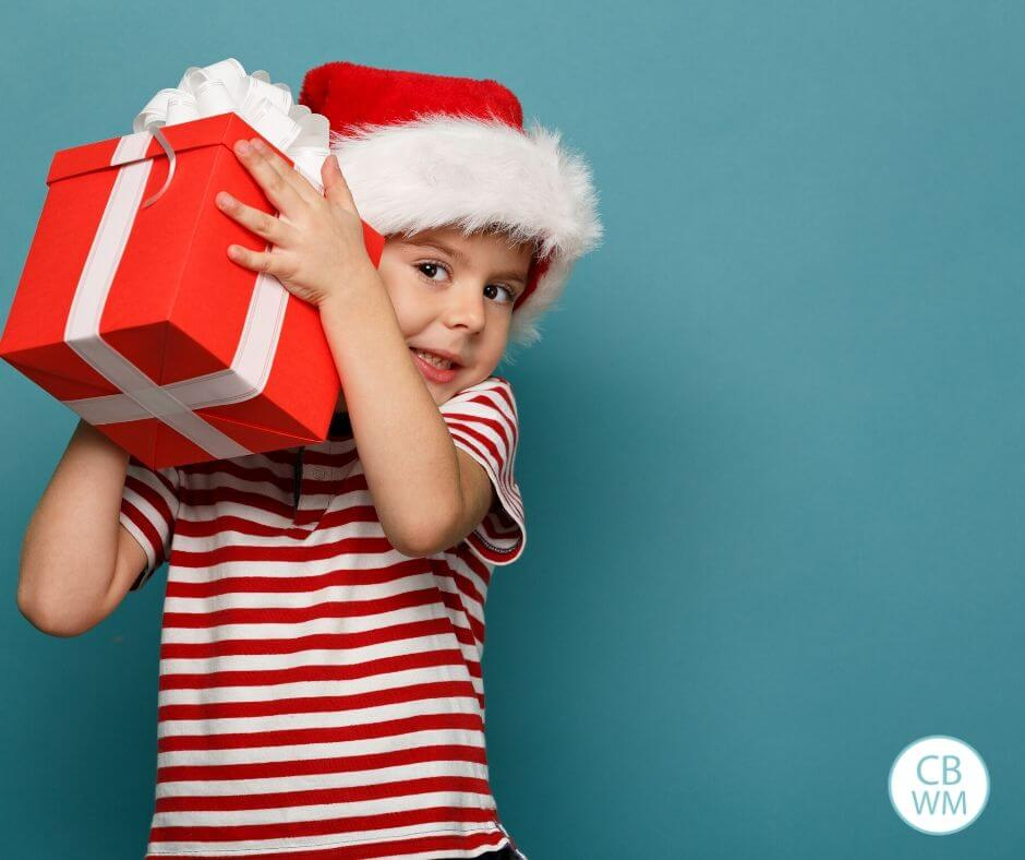 Child holding gift wrapped in red