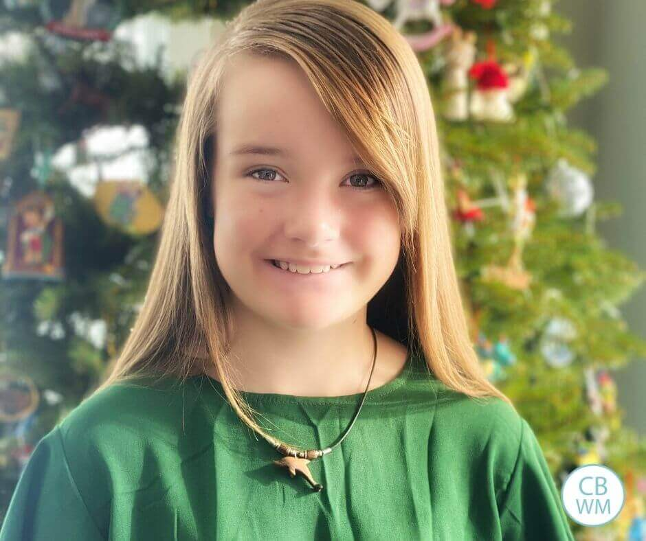 Kaitlyn in a green dress in front of a Christmas tree