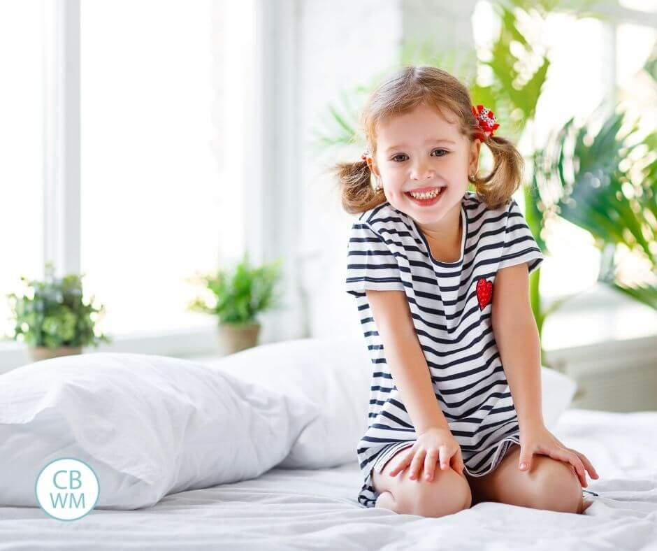Happy child sitting on the bed