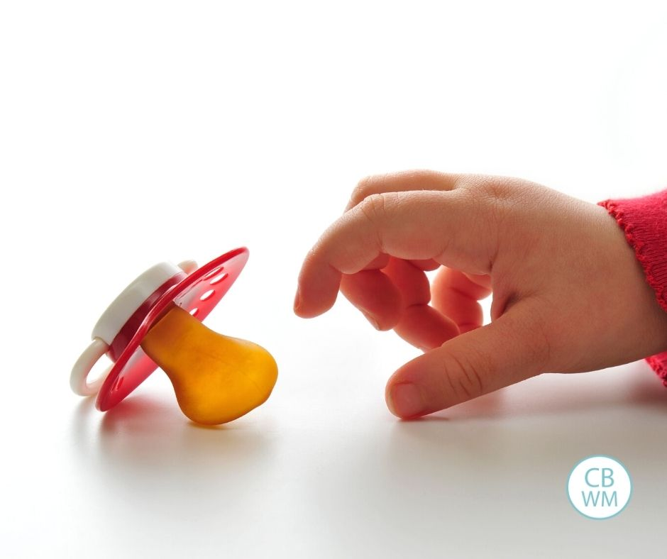Child reaching for pacifier