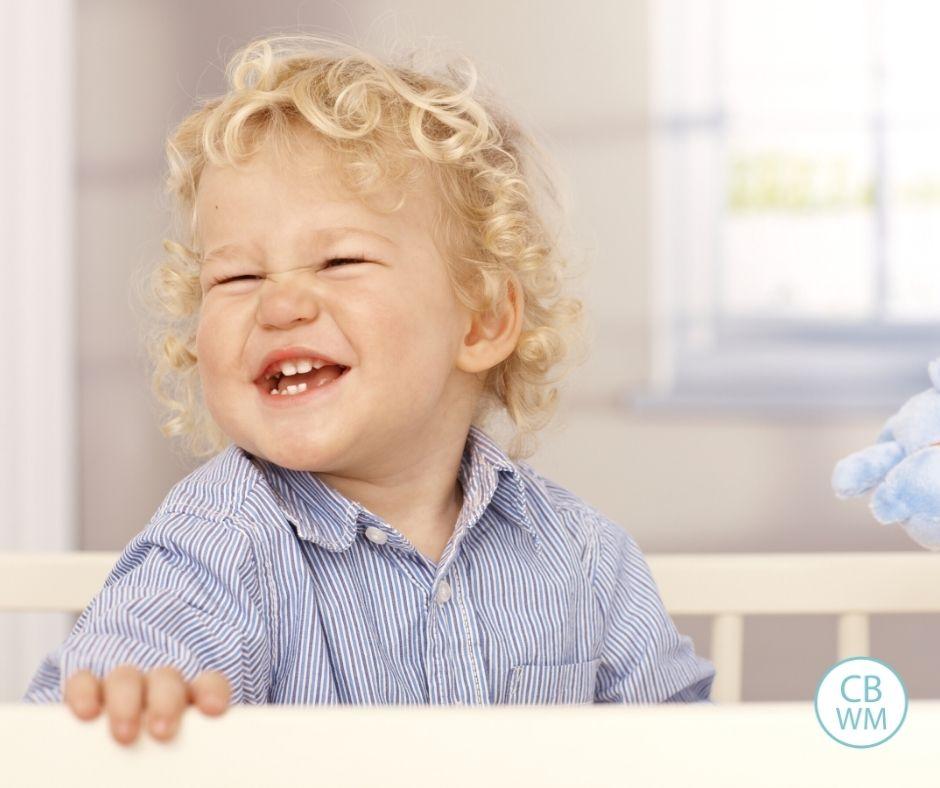 Toddler playing in a crib