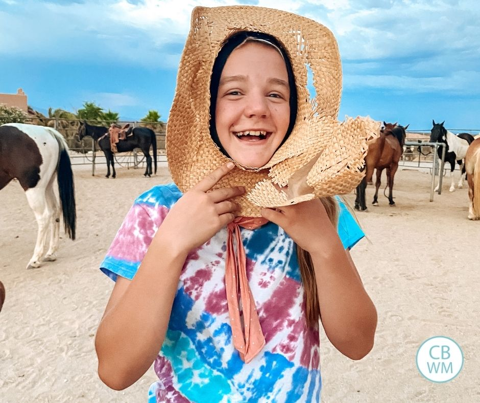 12 year old McKenna at a dude ranch holding a hat to her face